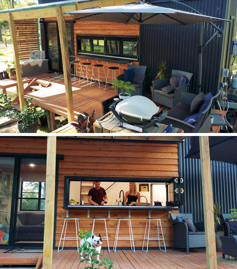 Designed for relaxing, the front porch of this tiny house is home to a casual lounge area with a bbq and a bar area. #TinyHouse #TinyHousePorch #TinyHouseDeck
