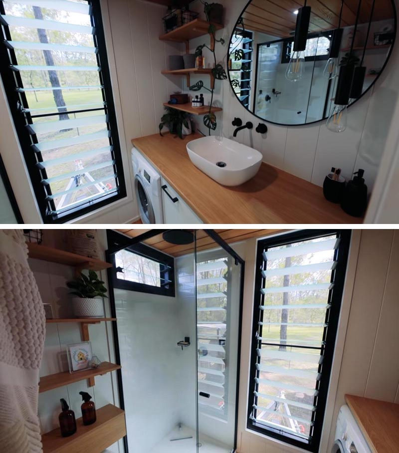 In this modern tiny house bathroom, there's a large vanity with that sits below a round mirror. There's also a full-size shower, a toilet, and a washing machine. #TinyHouseBathroom #SmallBathroom