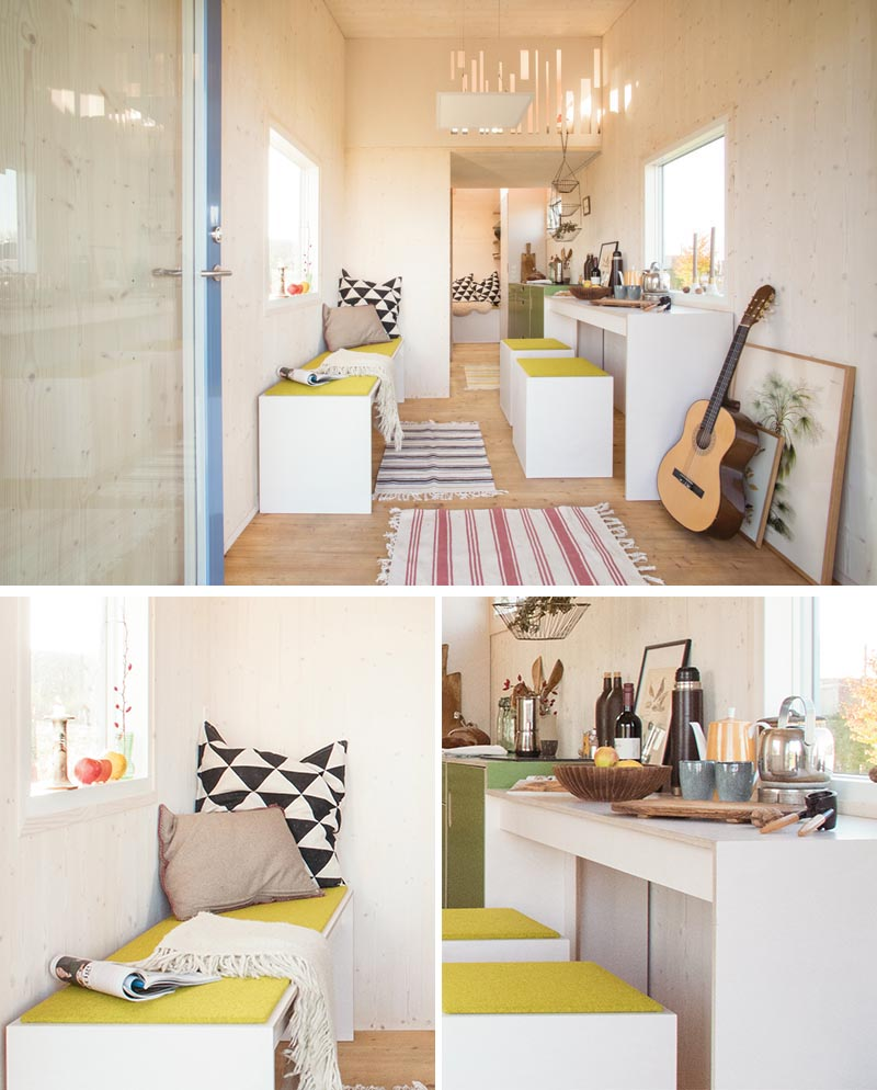 Inside this modern tiny house, there's a small open space before moving into a dining area with a bench, as well as a couple of stools and a table underneath the window. #TinyHouse #TinyHome #SmallLiving #TinyHouseDesign #TinyHouseLayout