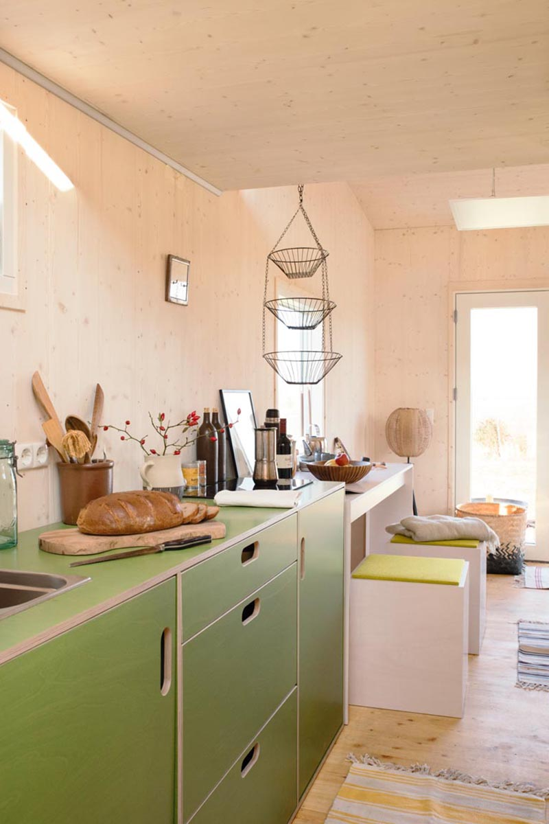 This modern tiny house has a kitchen that features minimalist green cabinets with cut-out handles. #TinyHouseKitchen #TinyHouseDesign #TinyHomeKitchen #SmallKitchen