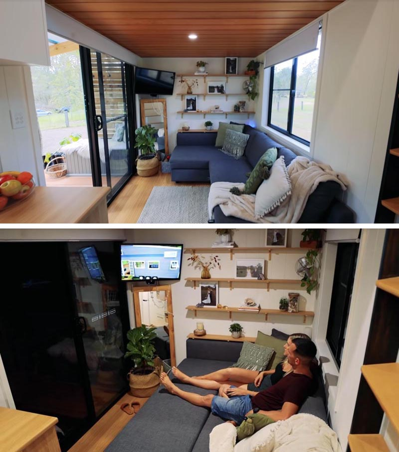 Stepping through the sliding doors of this modern tiny house, you're immediately in the living room that features a wall of wood bookshelves, and a regular size couch with hidden storage and a pull-out section that transforms it into a comfortable place to watch tv. #TinyHouse #TInyHouseLivingRoom #SmallLiving