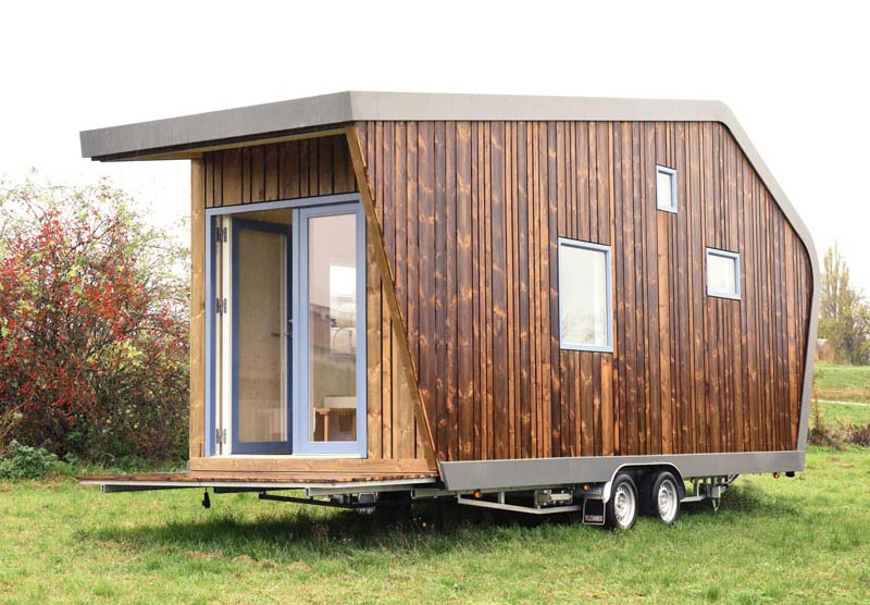 This modern tiny house is clad in wood and inside there's a dining area, kitchen, bathroom, desk, living area, and a lofted bedroom. #TinyHouse #ModernTinyHouse #TinyHome #SmallLiving #WoodSiding