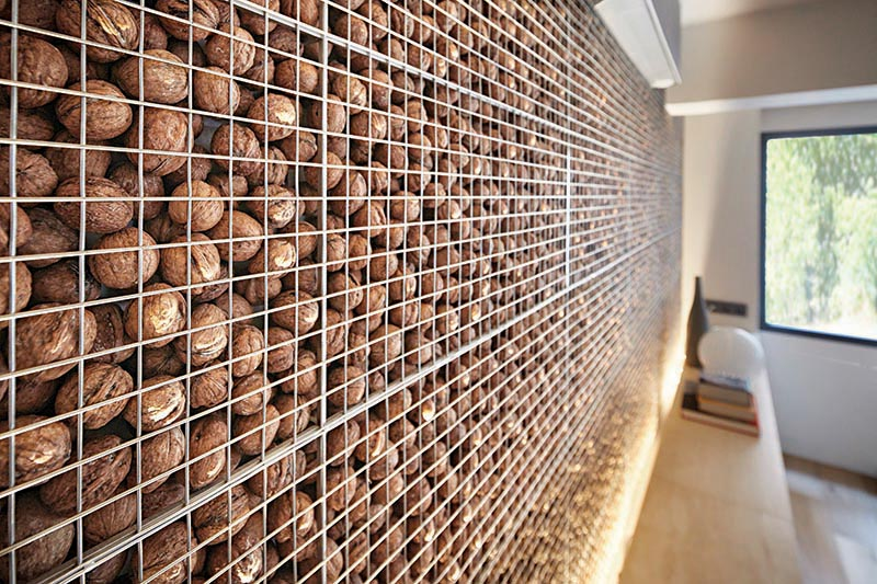 This modern home office features an eye-catching and unique accent wall that's created by filling a metal cage with walnuts, also known as a gabion. #AccentWall #UniqueAccentWall #FeatureWall #Walnuts #Gabion #HomeOffice