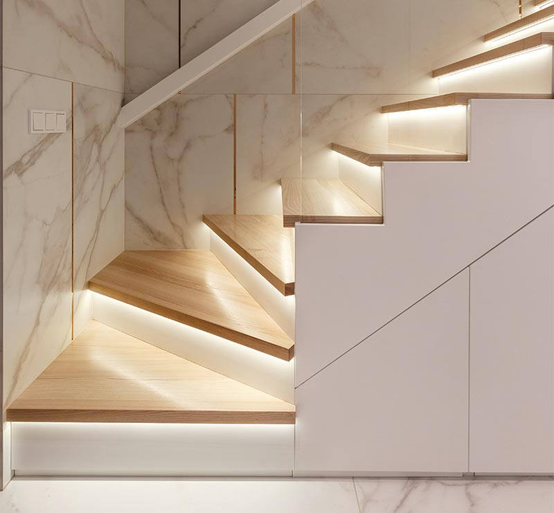 These modern wood stairs have a tread with an overhang (or nosing) that extends past the riser, allowing room for a thin strip of lighting to be attached to the underneath surface. #Stairs #StairsWithLighting #StairDesign #HiddenLighting