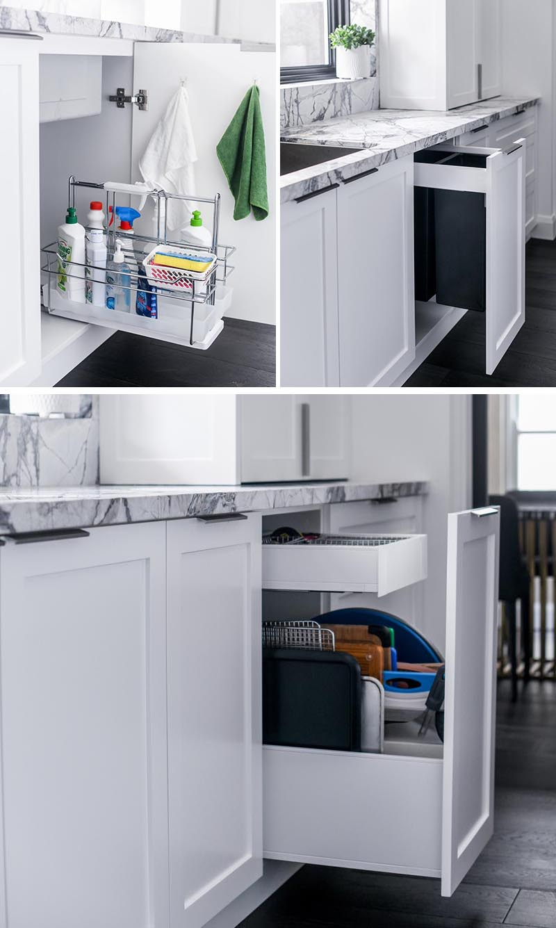 Underneath this kitchen sink, there's a cabinet with a pull-out caddy that holds a variety of cleaning products. In the adjacent cabinets, there's pull-out garbage and recycling bins, and a vertical drawer for storing baking trays and cutting boards. #KitchenDesign #KitchenIdeas #KitchenStorage #KitchenOrganization