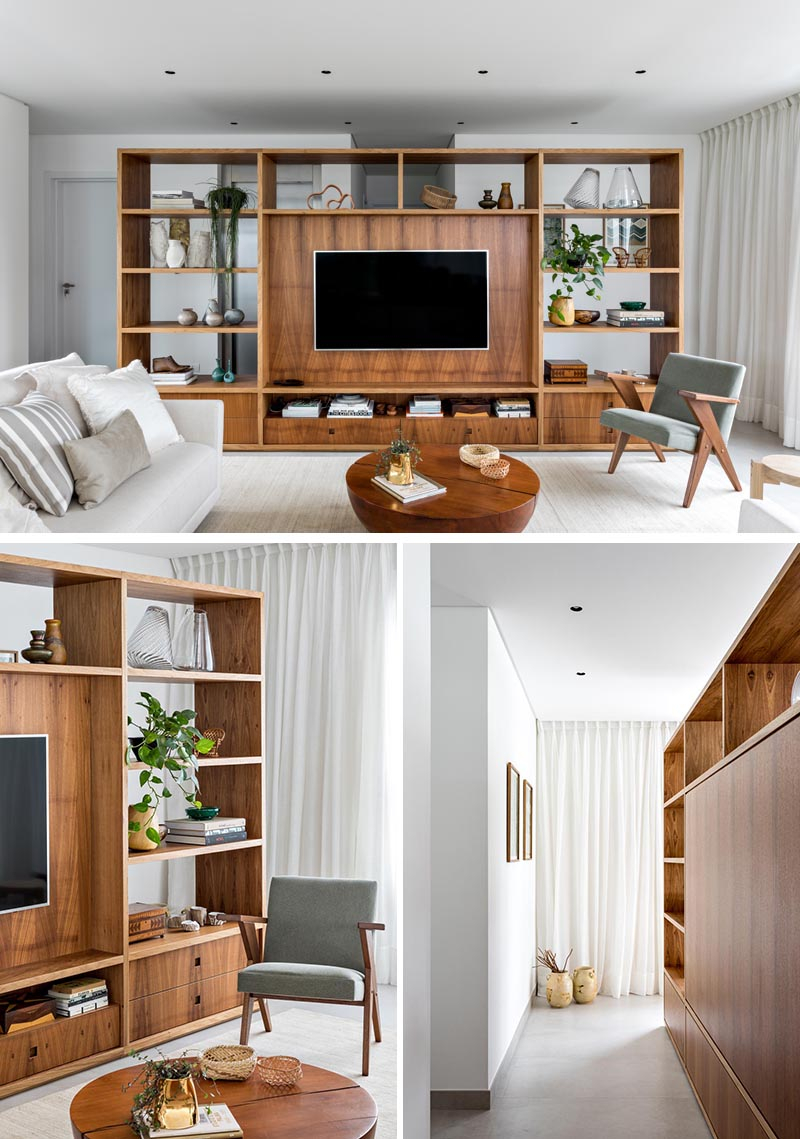 This modern room divider, made from Freijó wood, creates a space to welcome residents and visitors before reaching the open floor plan of the living room, kitchen, and dining area. From the living room side, the shelving unit provides a designated area for the TV in the living room, as well as storage in the form of bookshelves and drawers. #RoomDivider #WoodRoomDivider #WoodPartition #WoodShelving #LivingRoom #InteriorDesign #Interiors