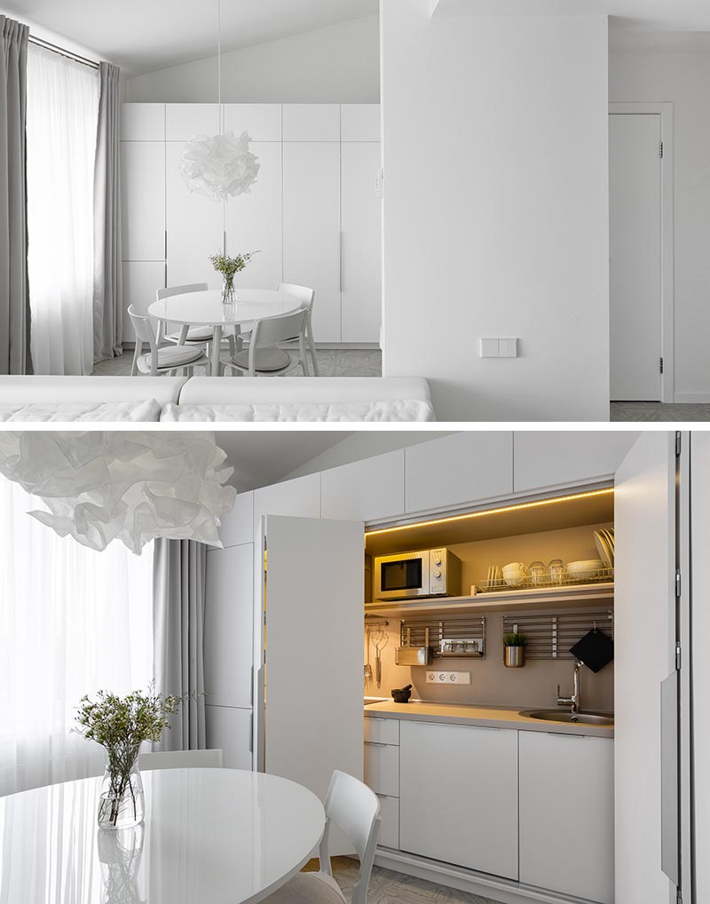 This modern and minimalist white apartment has the kitchen hidden within a closet in the dining area. #MinimalistKitchen #HiddenKitchen #KitchenDesign