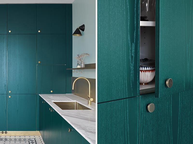 At the end of this modern kitchen, there's a wall of teal-stained wood cabinets that have small round bronze handles. Black scones provide additional light to the kitchen and tie in with the black tile featured on the floor. #TealCabinets #TealKitchen #KitchenIdeas #BronzeHardware