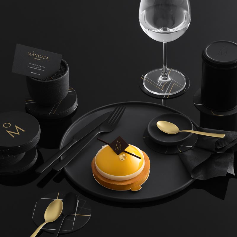 Matte black and gold plates and cutlery for a patisserie.
