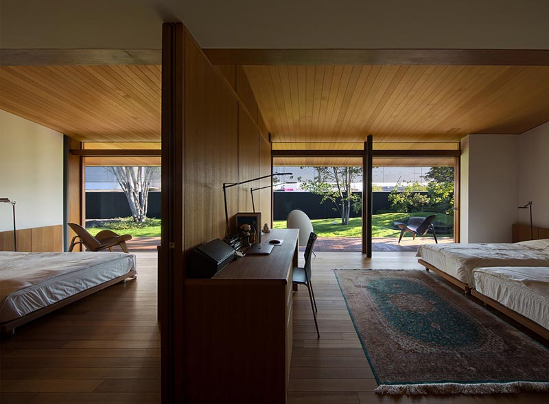 A wood wall separates two bedrooms and includes a desk.