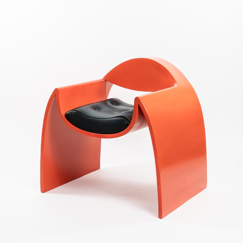 A curved armchair with a bright orange finish.