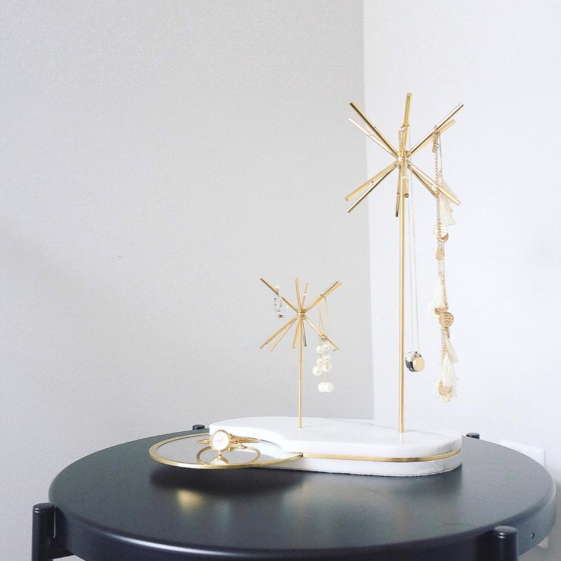 A modern white and gold jewelry stand.