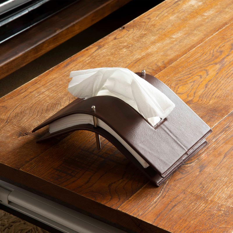 A modern tissue holder made from steel and leather.