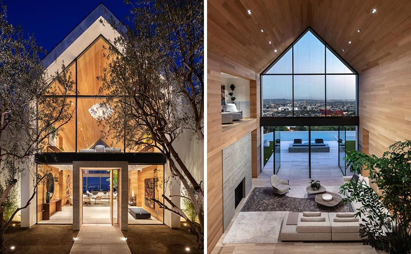 The eye-catching gabled design of this modern barn-inspired house, is easily seen upon approach to the house, and once inside, the wall of windows and doors at the other end of the wood-lined great room showcase the swimming pool and view. #ModernHouse #ModernArchitecture #HouseDesign #GabledRoof #GreatRoom