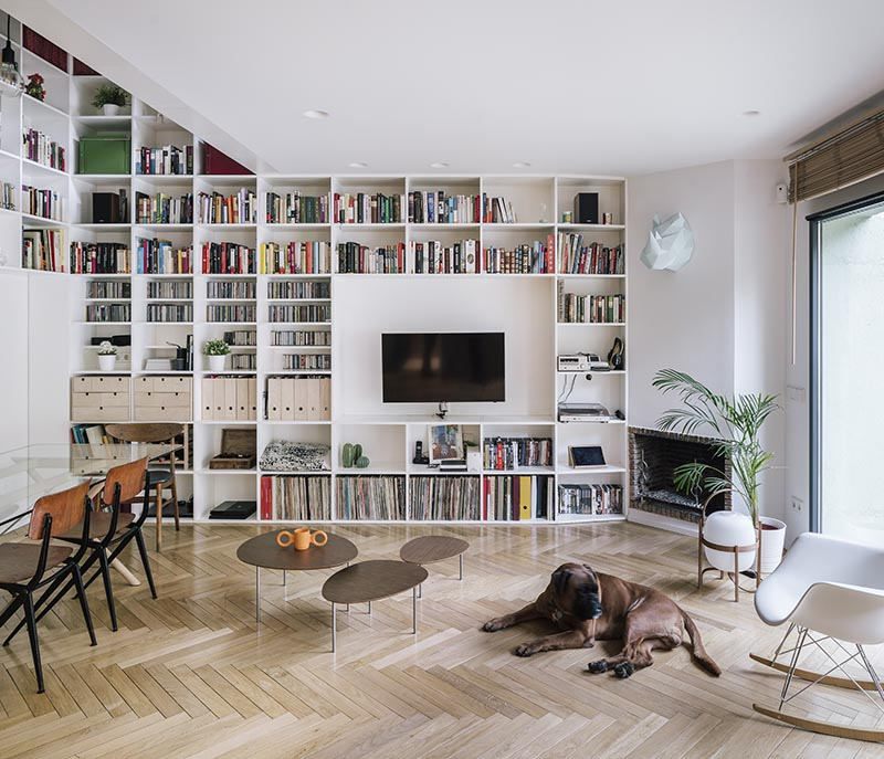 This modern white double-height bookshelf covers both the ground and first floor of this house. Starting in the open plan living room and dining room, the bookshelf wraps around the walls before traveling vertically towards the first floor of the house. #Bookshelf #DoubleHeightBookshelf #ShelvingIdeas #BuiltInBookshelf