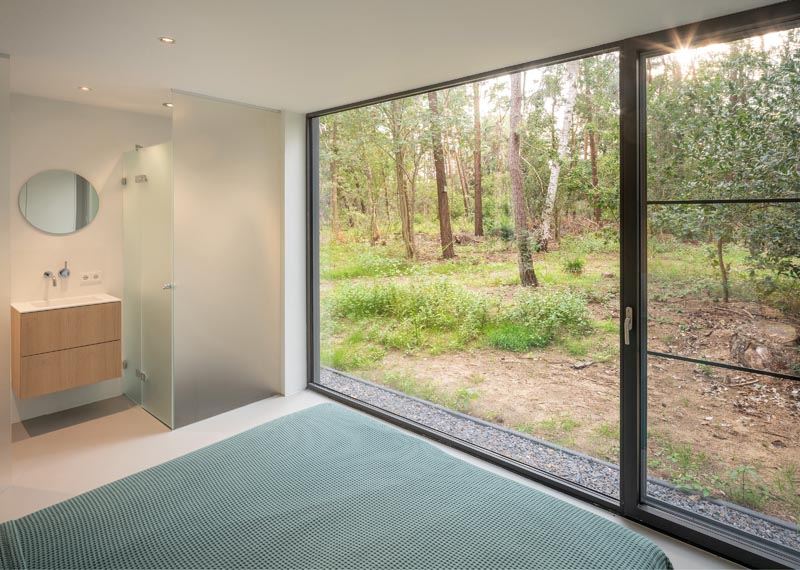 In this modern master bathroom, there's a large floor-to-ceiling picture window, as well as a bathroom that has a shower surrounded by a frosted screen. #FrostedShowerScreen #MasterBedroom #PictureWindow