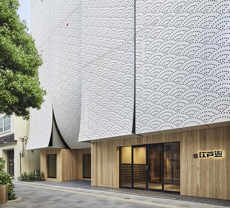 Kubo Tsushima Architects has designed Ryogoku Yuya Edoyu, a spa facility in Tokyo, Japan, that showcases an artistic facade of perforated aluminum in a traditional Japanese pattern. #ArtisticFacade #BuildingFacade #PerforatedAluminum #Architecture
