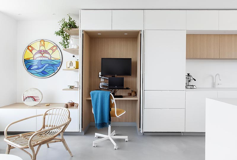 A small wood lined home office located within minimalist white  kitchen cabinets.