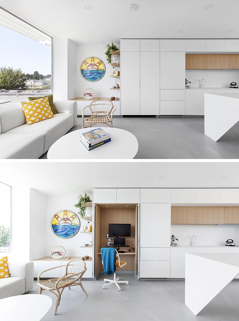 Minimalist white kitchen cabinets open to reveal a small wood lined home office.