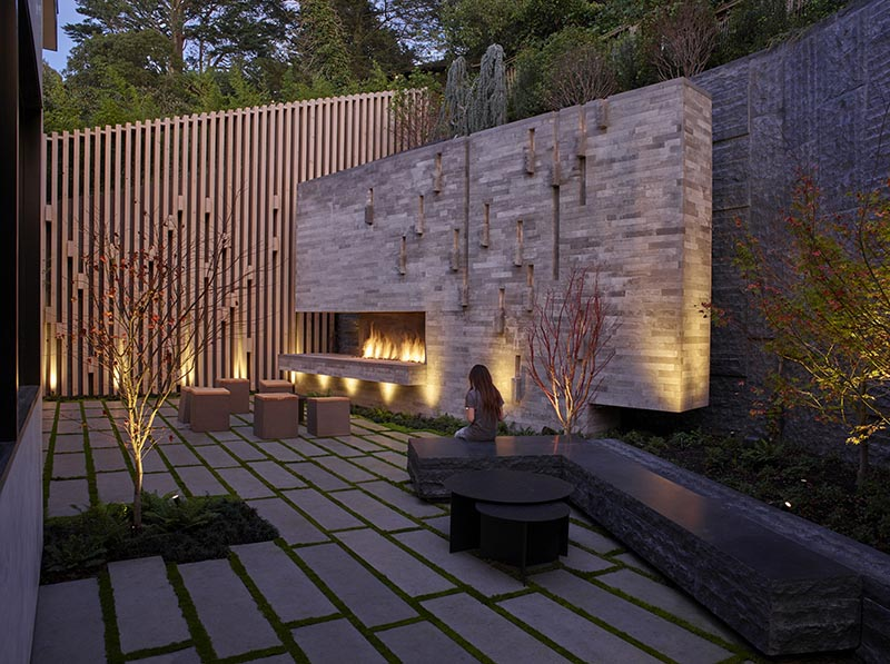 This modern courtyard has Basalt-clad retaining walls that hold back the hillside and frame the courtyard, while the limestone hearth anchors the garden, and a panel of blackened steel creates a backdrop for a built-in barbeque. #LandscapeDesign #Landscaping #Courtyard #RetainingWalls #OutdoorFireplace