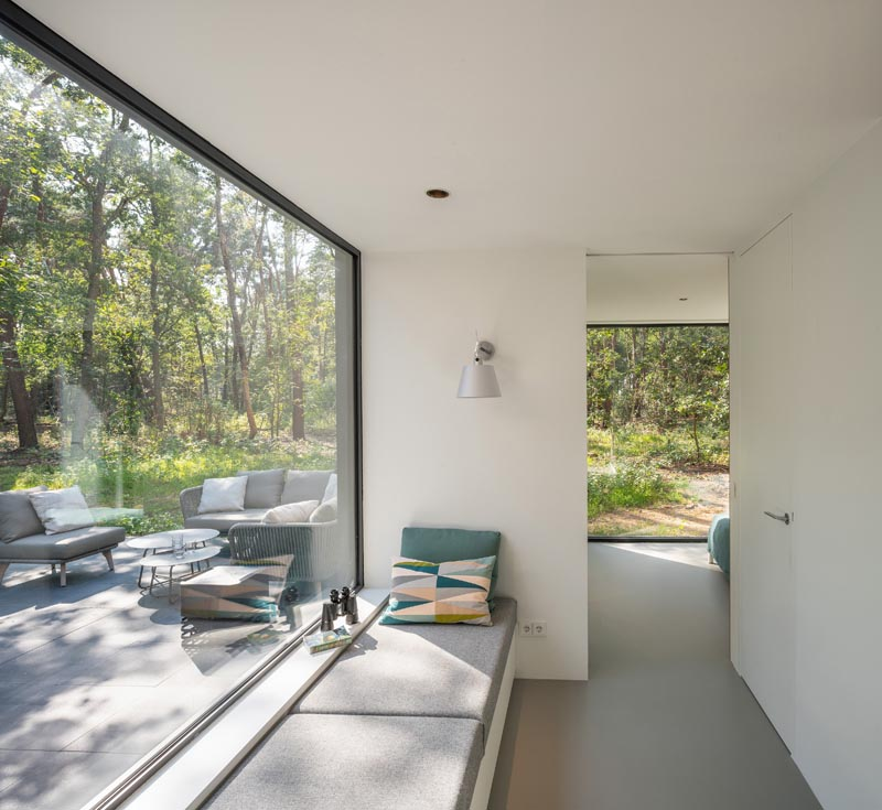 In a hallway that leads to the master bedroom, there's a built-in window seat next to a large picture window. #WindowSeat #PictureWindow #HallwayIdeas