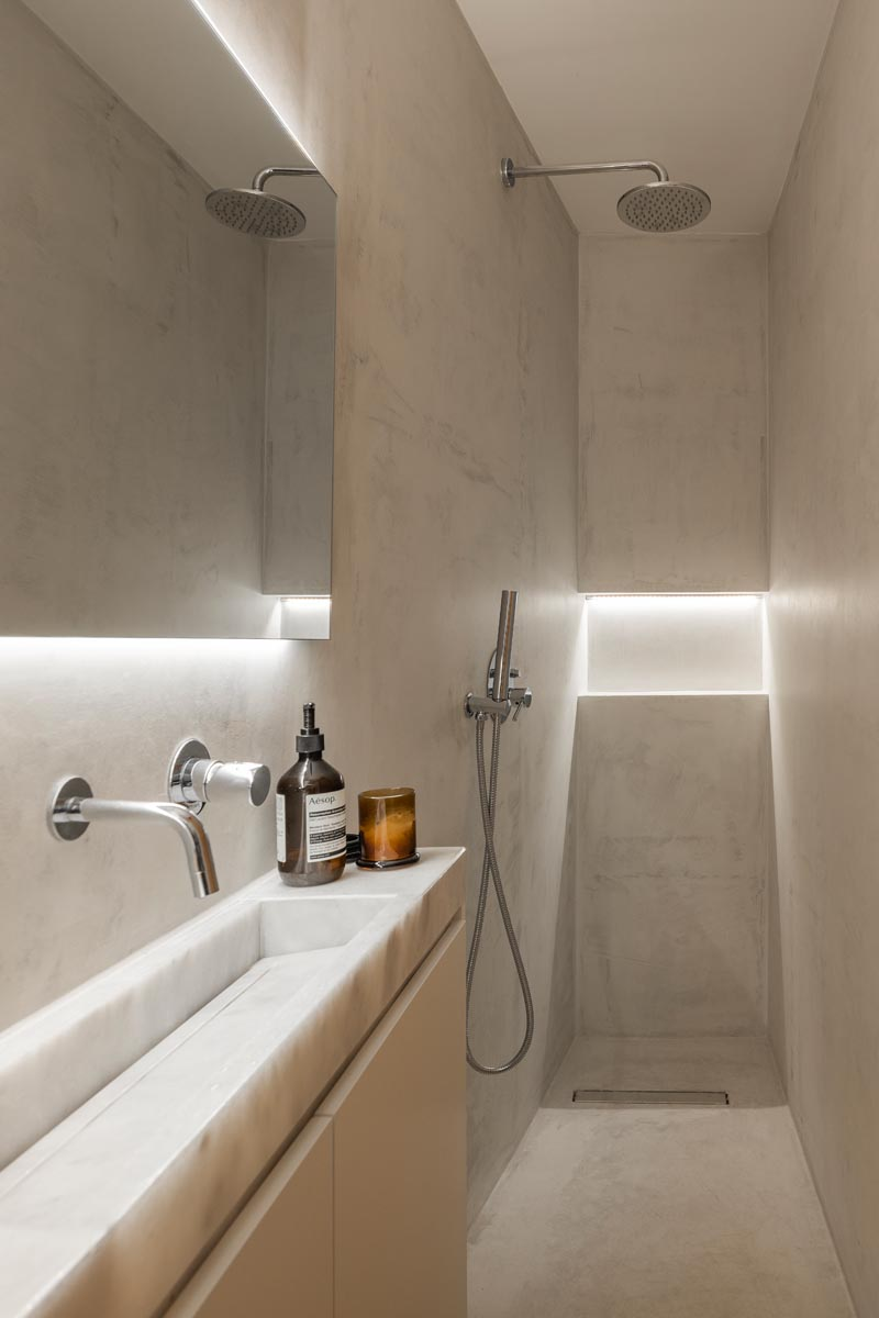 This small and narrow modern bathroom features a long thin vanity along one wall, with the shower at one end and the toilet at the other. Hidden lighting behind the mirror and in the shower niche help to keep the space bright. #SmallBathroom #NarrowBathroom #BathroomDesign #HiddenBathroomLighting #InvisibleDrain