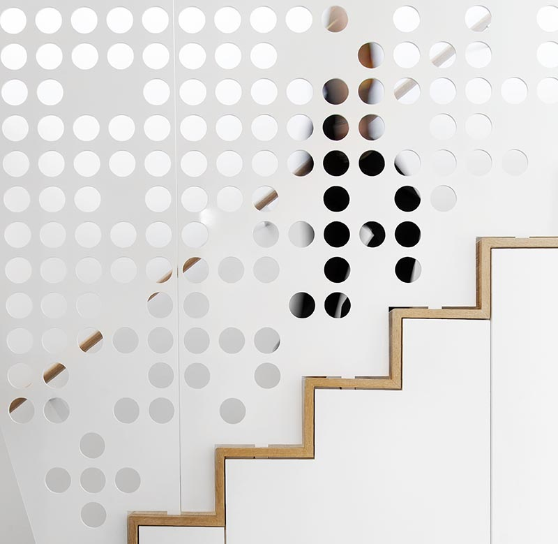In keeping with the mostly white interior of this modern apartment, a custom white perforated metal guardrail screen was designed for the stairs, creating a playful shadow effect that changes throughout the day. #GuardrailScreen #Stairs #StairDesign #ModernStairs