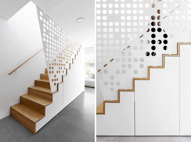 In keeping with the mostly white interior of this modern apartment, a custom white perforated metal guardrail screen was designed for these wood stairs, creating a playful shadow effect that changes throughout the day. #GuardrailScreen #Stairs #StairDesign #ModernStairs #Screen #PerforatedScreen