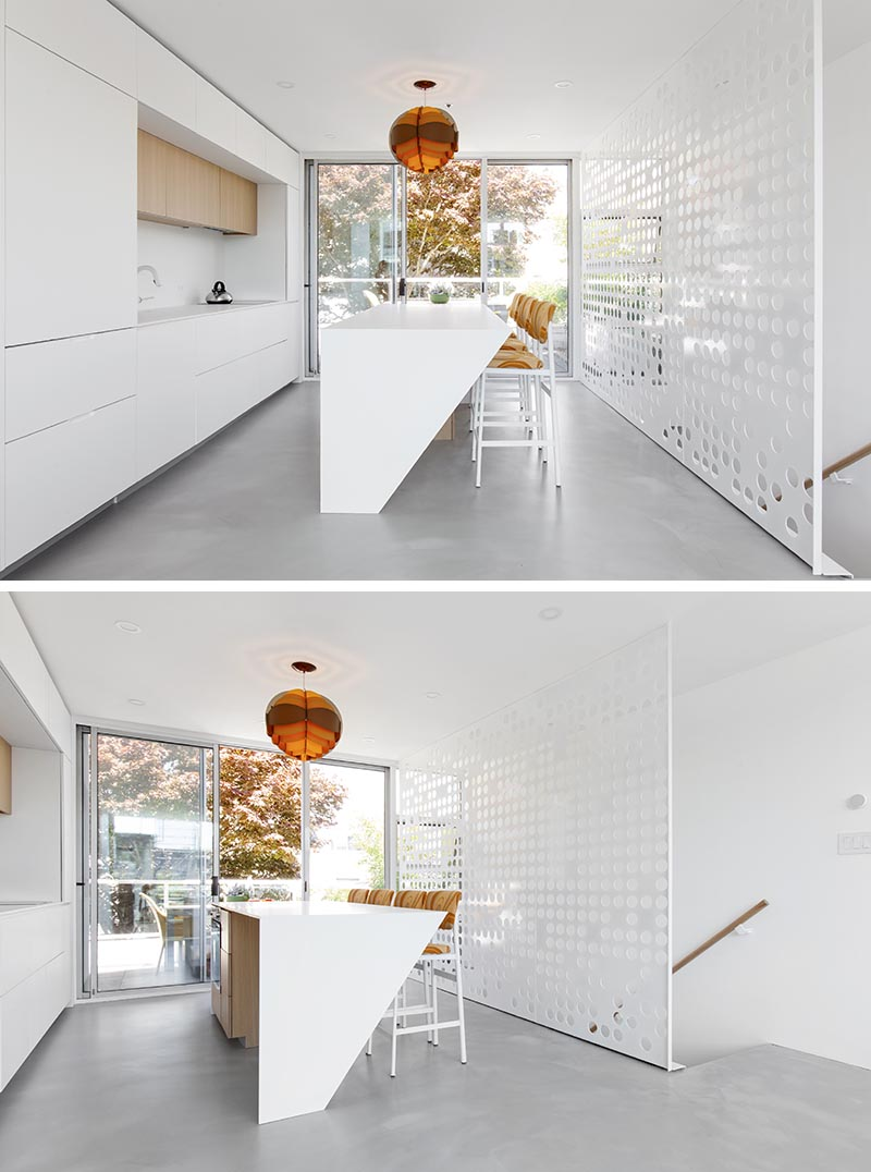 A custom white perforated metal guardrail screen was designed for this modern apartment. It doubles as a minimal and artistic backdrop for the kitchen. #GuardrailScreen #Stairs #StairDesign #ModernStairs #Screen #PerforatedScreen