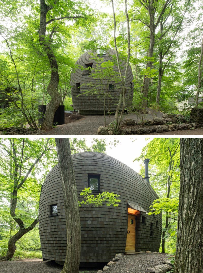 This small curved house was built using materials like local wood and clay, and crafted using traditional building techniques. Dark wood shingles cover the curved exterior, while recessed windows and skylights capture small amounts of natural light, and a light wood door welcomes guests. #CurvedHouse #SmallHouse #Shingles #Windows #Architecture