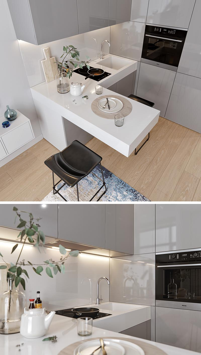 A small kitchen with an L-shaped countertop, integrated fridge, minimalist grey cabinets, hidden lighting, and a cantilevered peninsula for dining. #SmallKitchen #TinyKitchen #KitchenDesign #KitchenLayout #TwoBurnerCooktop