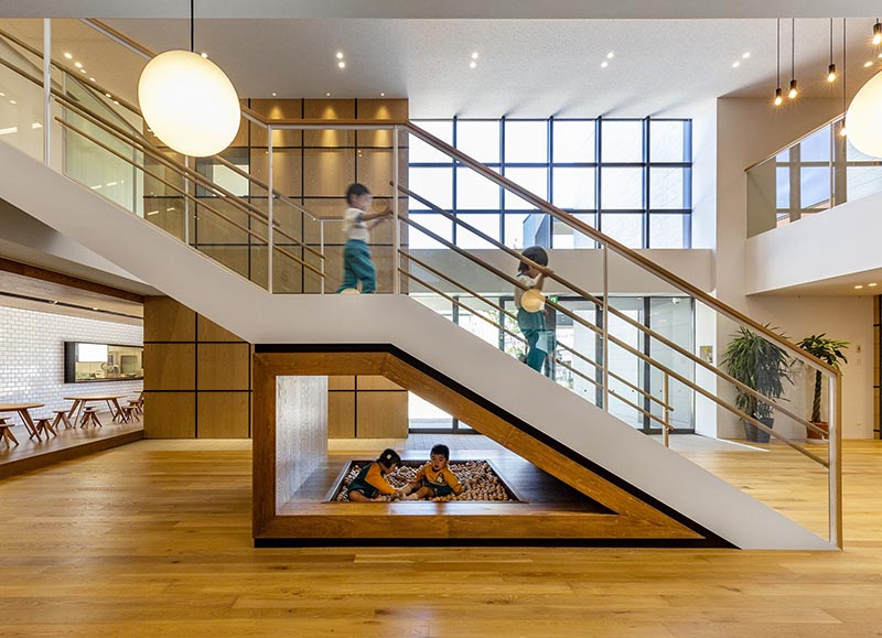 Located underneath the lower half of these kindergarten stairs is a wood framed area that's home to kids play area with a small ball pit. #KidsPlayArea #UnderStairDesign #KidsBallPit #InteriorDesign