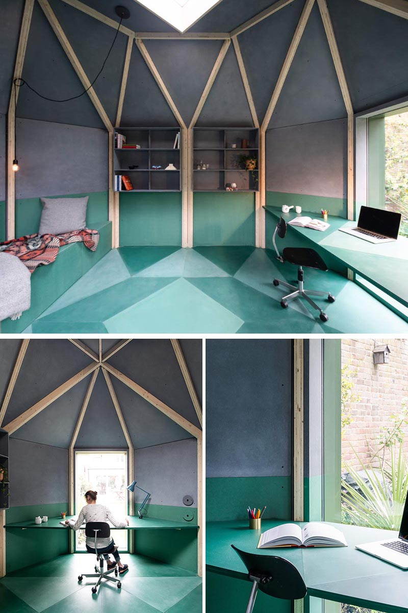 A modern backyard office with a geometric shape, a desk by the window, and a built-in bench with a fold out bed.