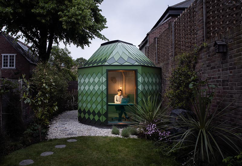 A backyard home office with a geometric design and green shingles.