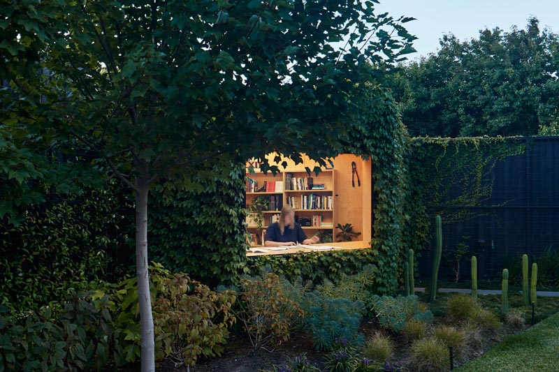A small backyard home office is covered in Boston ivy.