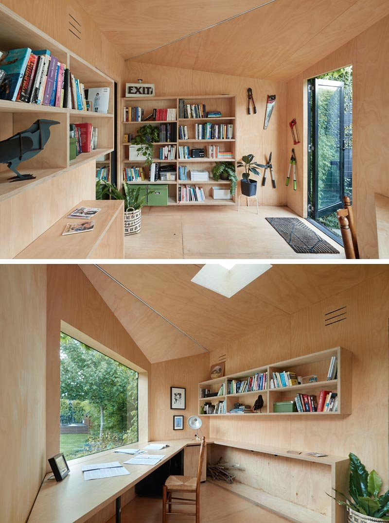 A small backyard home office has plywood walls, shelving, and a large desk.