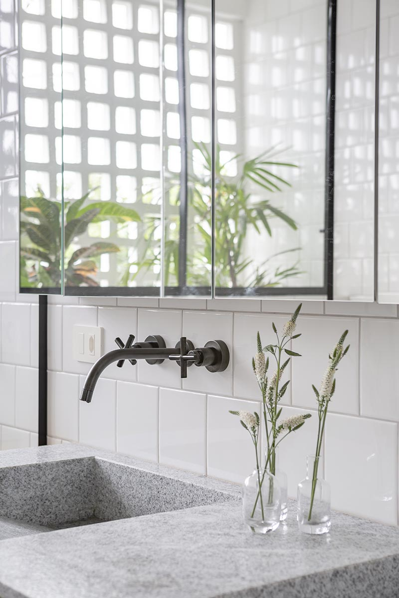 """The natural wood vanity in this modern bathroom is topped with a Brazilian grey and white granite named """"Branco Sao Paulo"""" in a matte finish, however it's the dual sinks with a sloped interior that are the focal point. #ModernBathroom #GraniteBathroomCountertop #GreyBathroom #ModernVanity"""