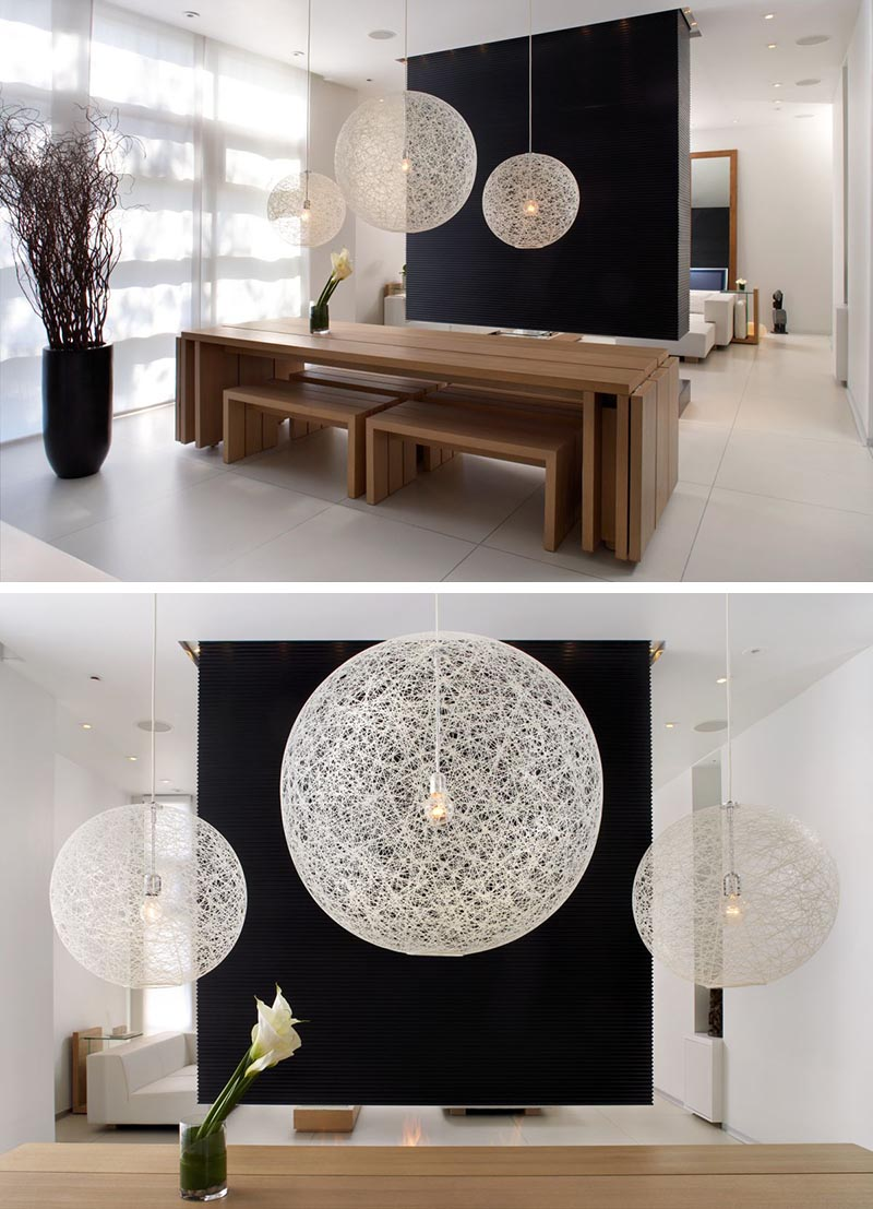A black room divider (or partition wall) creates a striking backdrop for the three white pendant lights above a wood dining table.