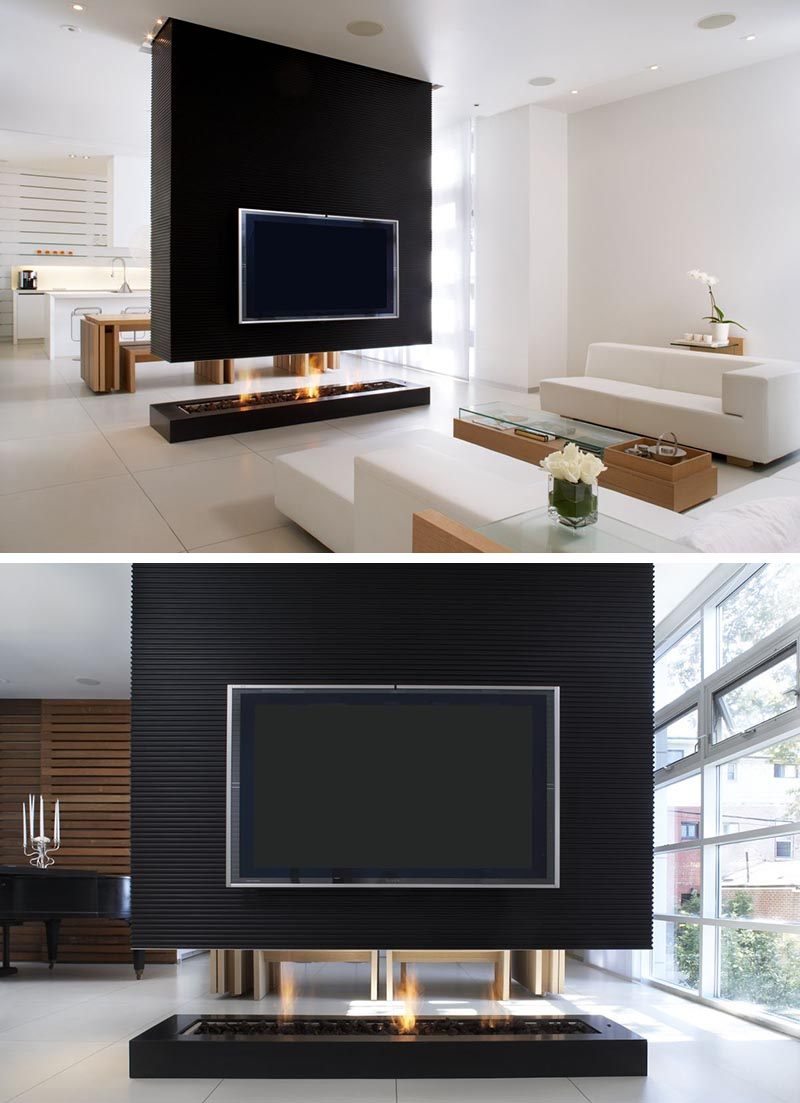 A black room divider has a recessed television and a see-through fireplace.