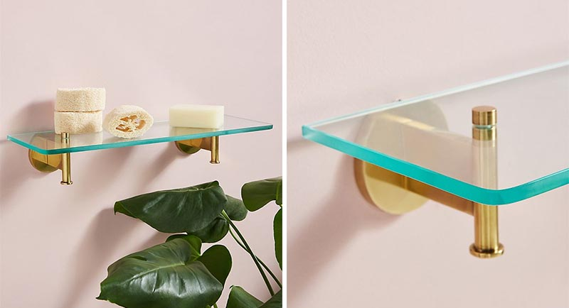 Modern bathroom shelf that has a thick glass top and brass supports.
