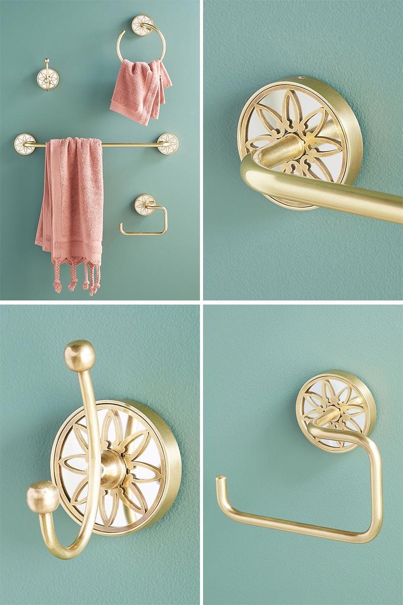 Metallic brass bathroom hardware with a delicate decorative motif.
