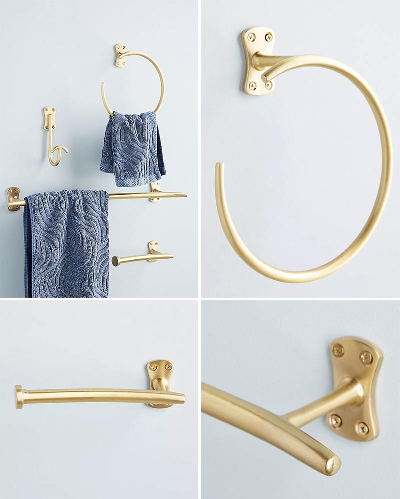 This modern brass bathroom hardware collection includes a towel bar, wall hook, toilet paper holder, and towel ring.