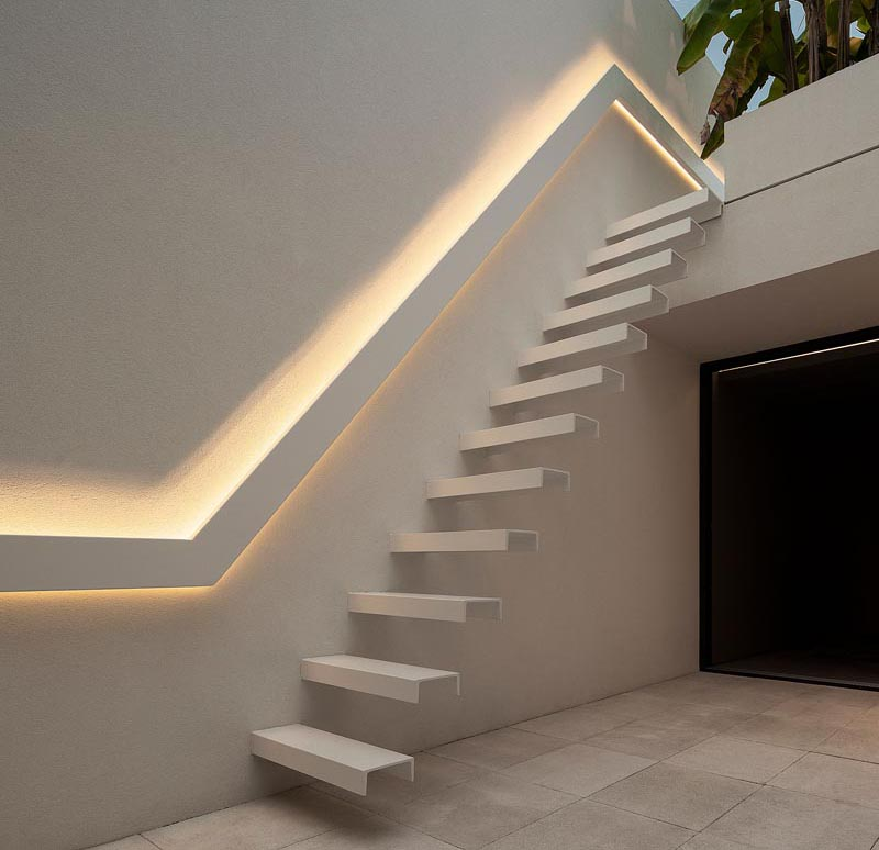A backlit handrail runs alongside cantilevered stairs.