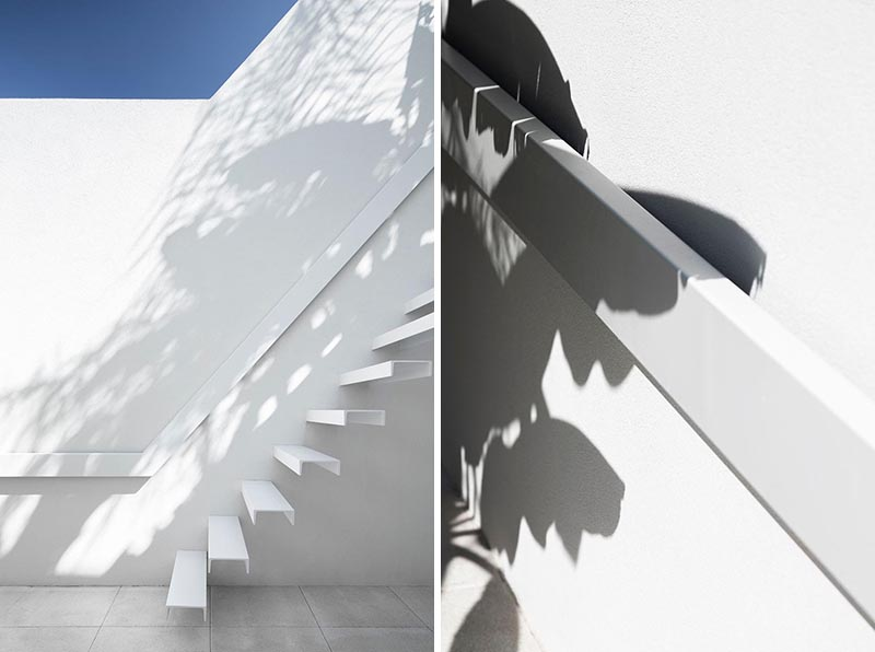 White cantilevered stairs with matching white handrail.