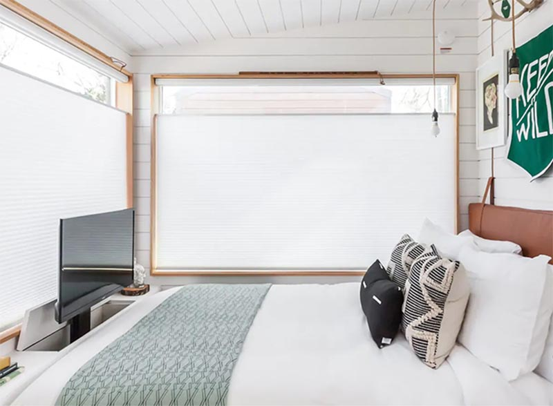 A television rises up from within a small cabinet at the end of the bed.