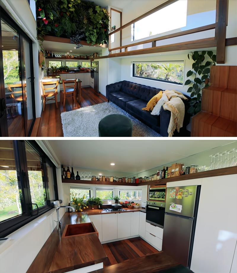 A modern tiny house with an open plan living room and kitchen, and an interior green wall.