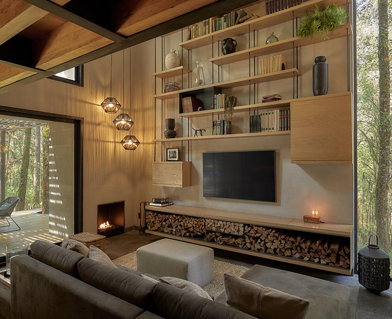 A modern living room with open wood shelving that lines the wall and includes firewood storage.