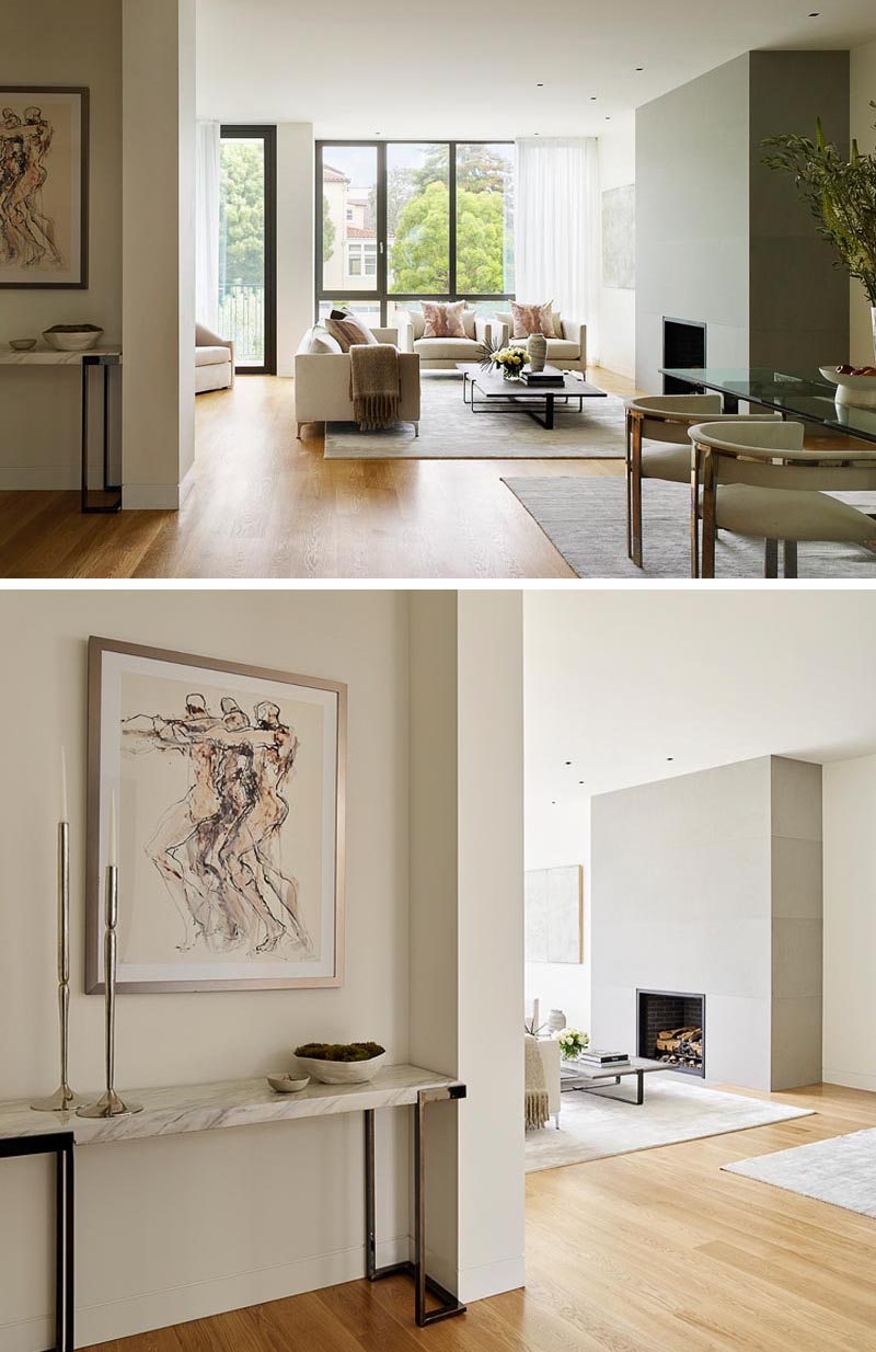 A fireplace with a smooth grey surround is the focal point of a living room with a neutral color palette.