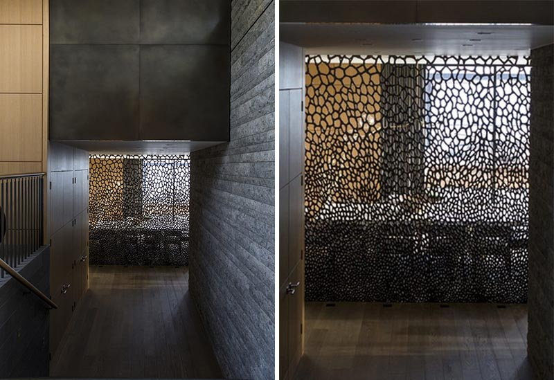 An artistic and sculptural bronze screen separates the dining room from the stairs.
