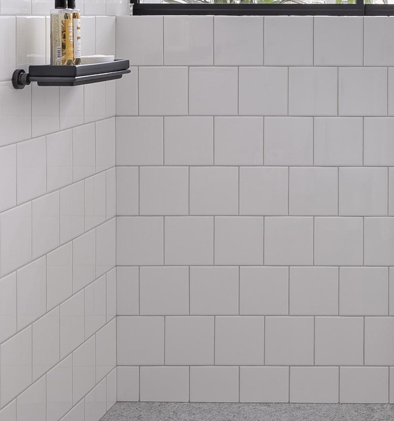 In this modern bathroom, floor-to-ceiling white tiles cover the walls, measure in at 15x15cm, have matching white grout. #SquareWhiteTiles #SquareTiles #BathroomIdeas